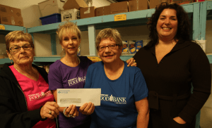 Tanis Webster, chair Empty Bowls, presents a $12,000 cheque to representatives from the Thunder Bay Food Bank (left to right) Myra Bjorn, Lynda Roussel, and Judy Smiegielski